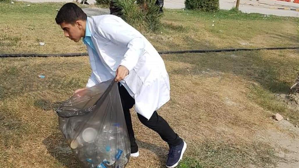 بالصور.. شباب متطوعون ينظفون مكان الاعتصام وسط النجف